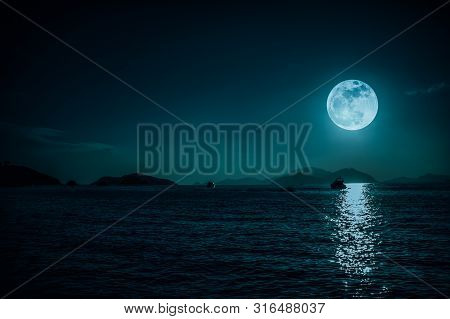 Scenic View Of Small Boat In Calm Sea Water At Night Time And Super Moon. Serenity Nature Background