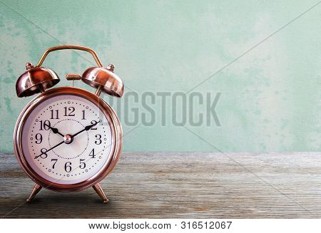 Retro Alarm Clock On A Wooden Table With Grunge Wall Background. Save Time Savings Daylight Up Retro