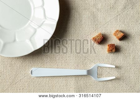 On The Table, Empty White Plate And Lying Next To The Crackers. A Fork With Broken Middle Teeth Symb