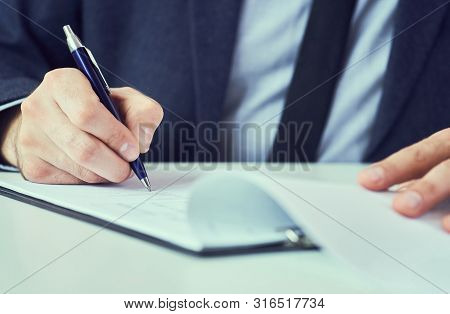 Hand Of Businessman In Suit Filling And Signing With Blue Pen Partnership Agreement Form Clipped To