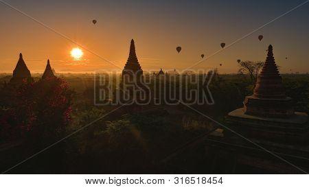 Hot Air Balloons Floating At Sunrise Over Bagan  Myanmar, Pagodas And Brick Monastery