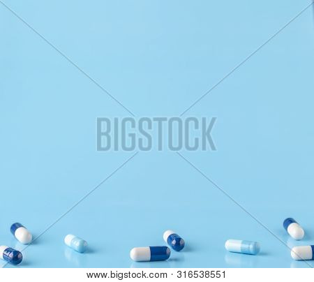 Various White-blue Medication Capsules. Blue Background With Text Space