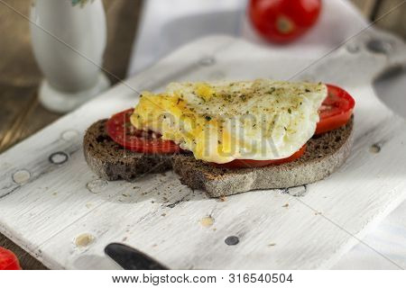 Poached egg on sourdough toast, with grilled tomatoes. A healthy, delicious breakfast or brunch. poster
