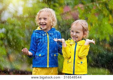 Kids Play In Autumn Rain. Child Playing Outdoor On Rainy Day. Little Boy Catching Rain Drops Under H