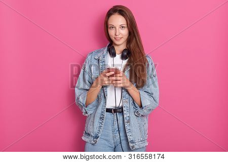 Portrait Of Happy Beautiful Young Lady Using Her Phone, Looking Directly At Camera And Smilng, Weari