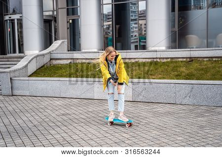 Blond Female Hipster Woman Riding On The Longboard In The Street At City.