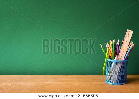 Back To School Concept, Blue Glass With School Supplies On A School Desk On A Background Of A Clean