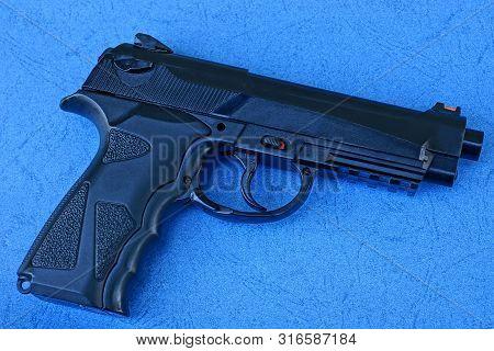 One Big Black Pneumatic Gun Lies On A Blue Table