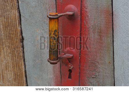 Old Red Doorknob On Gray Wooden Door Boards