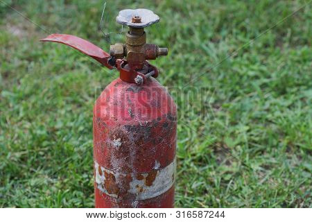 Red Old Fire Extinguisher With A Valve On A Background Of Green Grass