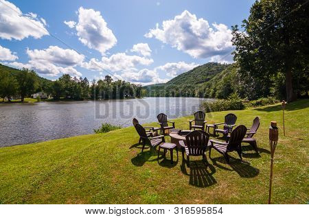 A Fire Pit Surrounded By Adirondack Chairs Next To The Allegheny River In Warren County, Pennsylvani