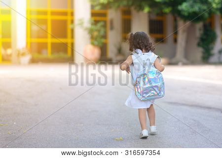 Curly Cute Little Toddler Girl Back To School With Holographic Schoolbag Or Satchel, Child Walking T