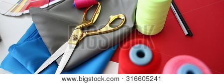 Fashion Designing Tailor Craftsmanship Concept. Fabric, Color Palette and Sewing Tools on Table. Needle Machine Bobbins Spools of Thread with Gold Scissors on Silk Piece. Designer Working Desk poster
