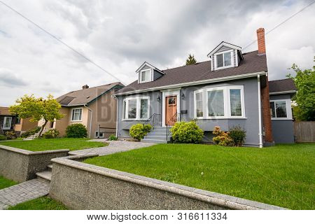 Average Residential House With Green Lawn On Land Terrace