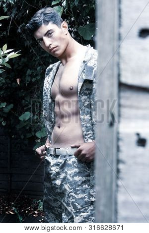 Handsome soldier with open uniform shows off muscular abs and pecs while standing next to wooden hut poster