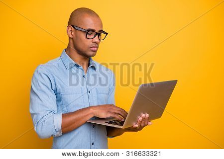 Photo Of Dark Skin Business Man Not Smiling Browsing Notebook Wear Specs Jeans Denim Shirt Isolated