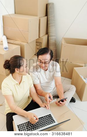 Aged Asian Husband And Wife Ordering Movers Online When Sitting In Apartment Full Of Belongings