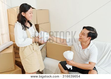 Smiling Father Giving Wrapped Glasses And Cups To His Smiling Teenage Daughter When They Are Unpacki