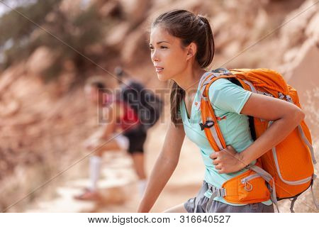 Hike travel Asian hiker woman carrying heavy backpack tired on outdoor trek in Grand Canyon trail walking up the mountain. Active healthy lifestyle.