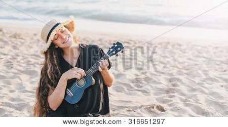 Beautiful Young Woman With Long Curly Healthy Hair Wearing Trendy Straw Hat Playing Ukulele At The B