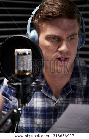 Voiceover Artist In Recording Studio Reading From Script Into Microphone