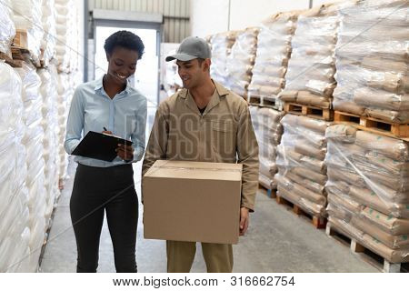 Front view of male worker and female manager discussing on clipboard in warehouse. This is a freight transportation and distribution warehouse. Industrial and industrial workers concept