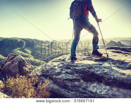 Happy Man Hiker Hold Medicine Stick,  Injured Knee Fixed In Knee Brace Feature. Scenic Mountain Top