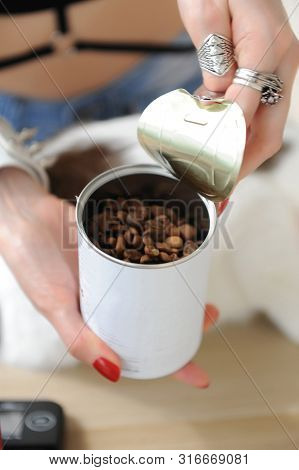 Barista girl opens tin can with coffee close up. Freshly roasted. Red manual grinder. White cat poster
