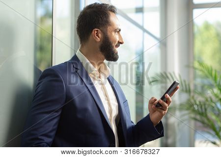 Cheerful Young Brunette Man Looking At Window