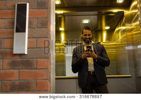 Cheerful Young Man Staring At His Telephone