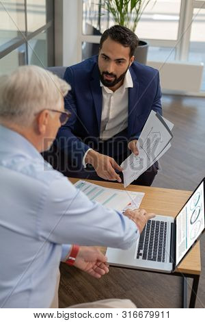 Serious Bearded Businessman Listening To Business Plan