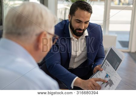 Concentrated Bearded Man Pointing At World Map