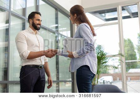 Joyful Bearded Man Standing In Front Of His Colleague