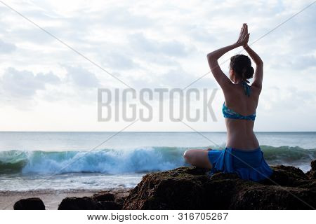 Young woman meditating, practicing yoga and pranayama with namaste mudra at the beach. Lotus yoga pose with namaste mudra. Caucasian woman sitting on the rock. Sunset time. Yoga retreat in Bali Indonesia