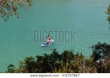 Young Woman Paddling On Sup Board On The Tropical Beach. Active Summer Vacations With Paddle Board,