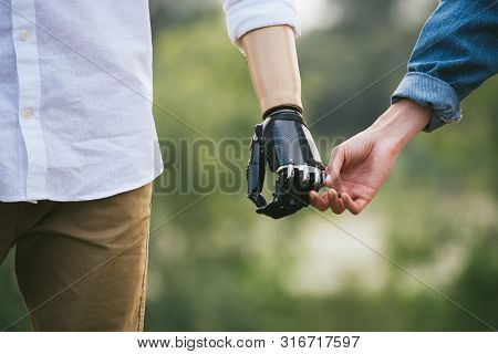 Closeup Shot Of Man With A Prosthetic Limb Holding Hands With Female Partner, Gentle Touch, Outdoor