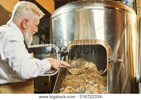 View From Back Of Man Keeping Shovel And Examining Quality Of Grist In Brewery. Professional Man In