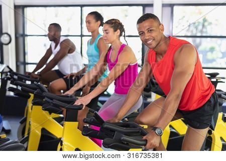 Side view of diverse fit people exercising on exercise bike in fitness center. Bright modern gym with fit healthy people working out and training at spin class