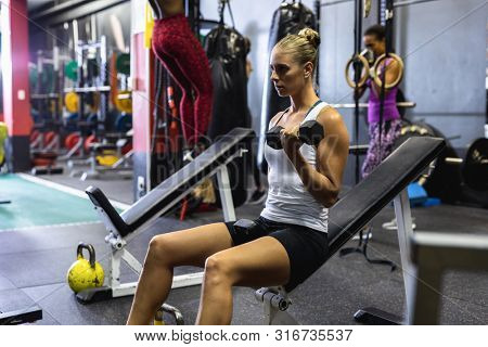 Side view of Caucasian Female athlete exercising with dumbbells on a ab bench in fitness center. Bright modern gym with fit healthy people working out and training