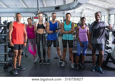 Portrait of diverse fit people standing together in fitness center. Bright modern gym with fit healthy people working out and training