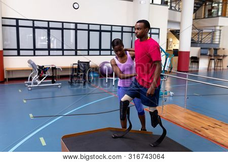 Front view of African-american Female physiotherapist helping disabled African-american man walk with prosthetic leg on ramp in sports center. Sports Rehab Centre with physiotherapists and patients