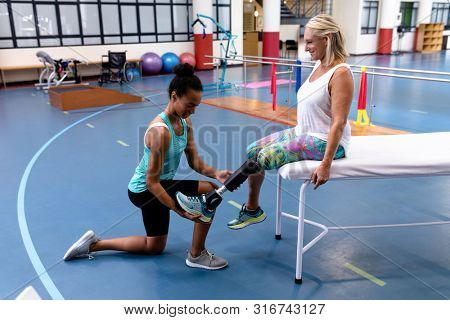 Side view of African-american female trainer adjusting prosthetic leg of disabled Caucasian active senior woman in sports center. Sports Rehab Centre with physiotherapists and patients working