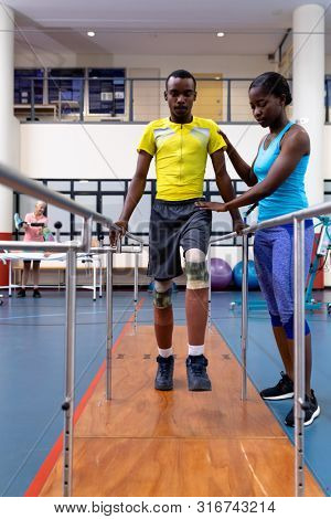 Front view of African-american Female physiotherapist helping disabled African-american man walk with parallel bars in sports center. Sports Rehab Centre with physiotherapists and patients working