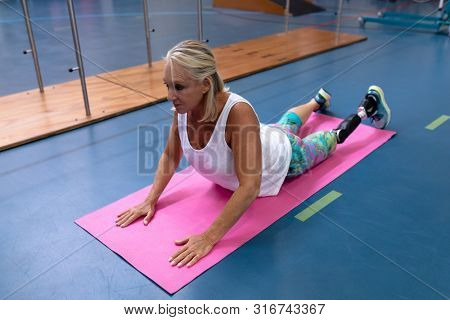 Front view of disabled Caucasian active senior woman exercising on exercising mat in sports center. Sports Rehab Centre with physiotherapists and patients working together towards healing