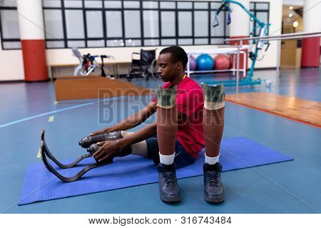 poster of Side view of African-american disabled man exercising on exercise mat in sports center. Sports Rehab Centre with physiotherapists and patients working together towards healing