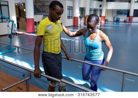 Front view of African-american female physiotherapist assisting disabled African-american man walk with parallel bars in sports center. Sports Rehab Centre with physiotherapists and patients working