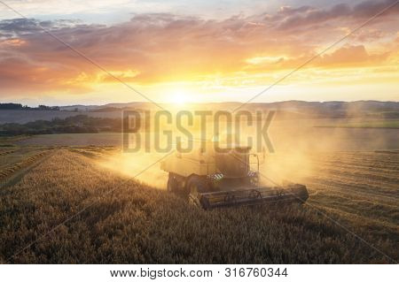 Harvesting of wheat in summer. Yellow harvester working in the Europian field. Combine harvester agricultural machine collecting golden ripe wheat on the field. View from above - aerial image