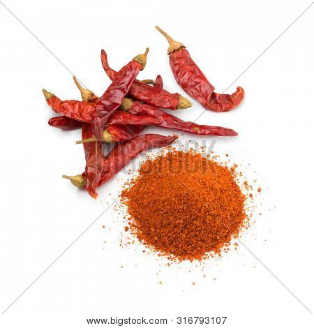Heap of dried red chili peppers and a heap of chili powder isolated on white background
