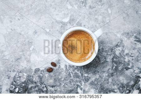 Cup Of Coffee And Coffee Beans On Bright Stone Background. Top View. Copy Space