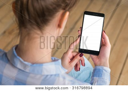Mockup Image: Woman Looking At Black Smartphone With White Blank Screen. Close Up View Of Woman Hand